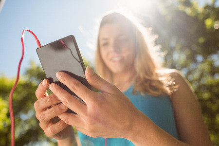 Fit blonde texting on her smartphone on a sunny day
