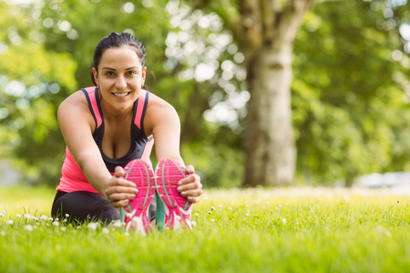 touching toes: Cheerful fit brunette stretching on the grass in the park Stock Photo