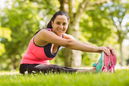 touching toes: Happy brunette in sportswear stretching on the grass in the park