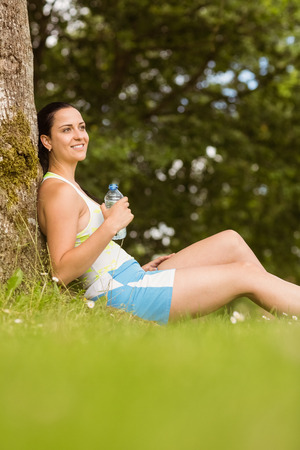 Cheerful fit brunette sitting against a tree holding a bottle in the park