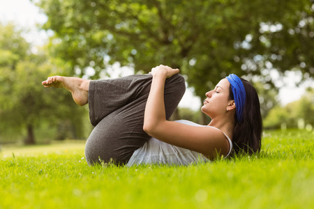 Content brunette doing yoga on grass in the park