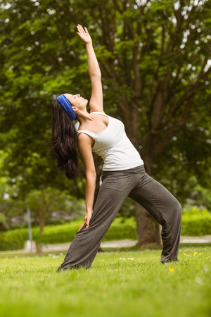 Cheerful brown hair doing yoga on grass in the park