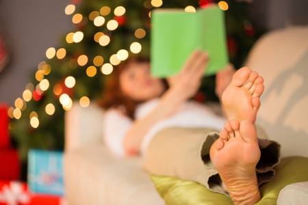 pelirrojas: Mujer tumbada en el sofá descalza lectura en casa, en la sala de estar Foto de archivo