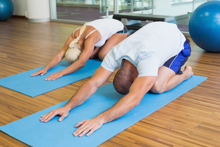 male and female: Sporty young couple in bending posture at the fitness studio