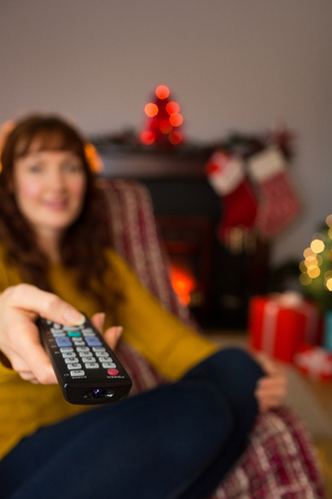 changing channels: Woman changing channels with remote control at christmas at home in the living room