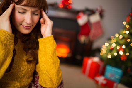 dolor de cabeza: Redhead conseguir un dolor de cabeza el d�a de Navidad en casa en la sala de estar
