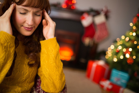 Redhead getting a headache on christmas day at home in the living room Stock Photo