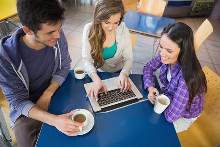 internet cafe: Los j�venes estudiantes que realizan misiones en la computadora port�til juntos en la universidad Foto de archivo