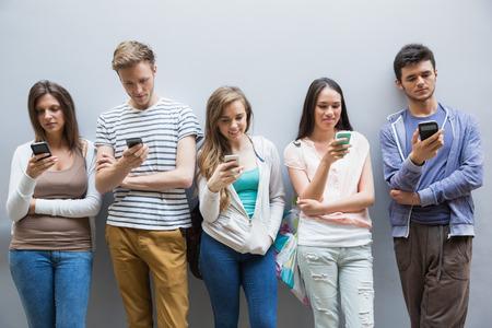 fila de personas: Los estudiantes que usan sus tel�fonos inteligentes en una fila en la universidad