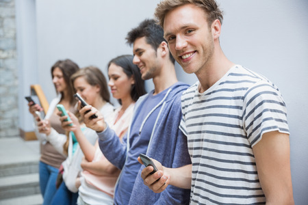 text message: Students using their smartphones in a row at the university