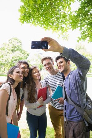 alumnos estudiando: Estudiantes felices que toman una Autofoto fuera en el campus de la universidad Foto de archivo