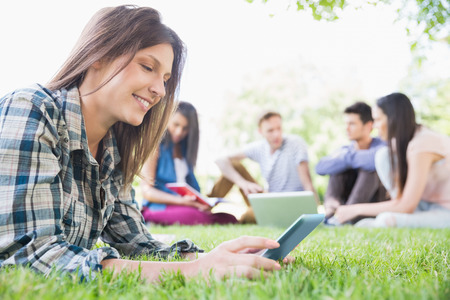 Happy students sitting outside on campus at the university photo
