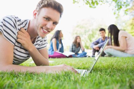 jovenes estudiantes: Estudiante feliz que usa su computadora port�til fuera de la universidad