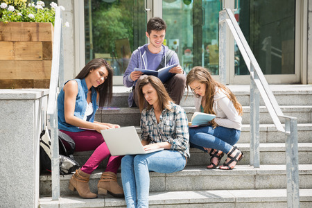 Students sitting on steps studying at the university photo