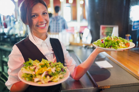 Pretty barmaid holding plates of salads in a bar Foto de archivo