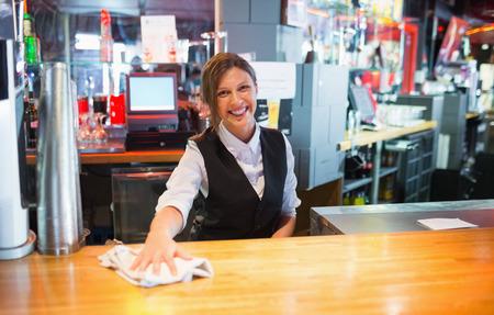 wiping: Pretty barmaid wiping down bar in a bar