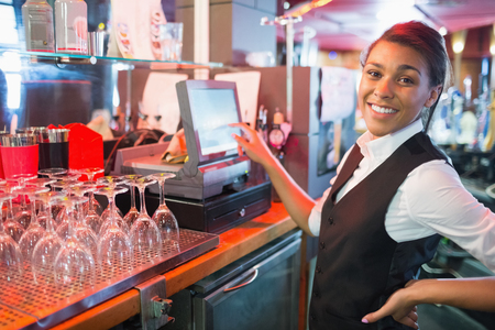 to till: Pretty barmaid using touchscreen till in a bar Stock Photo