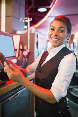 till: Pretty barmaid using touchscreen till in a bar Stock Photo