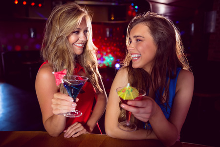 Pretty friends drinking cocktails together at the nightclub Stock Photo