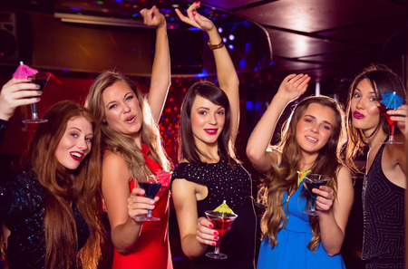 girls night out: Pretty friends drinking cocktails together at the nightclub Stock Photo