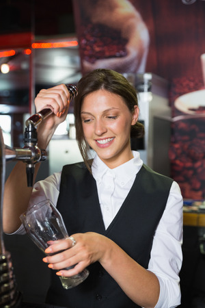 beer pump: Happy barmaid pulling a pint of beer in a bar