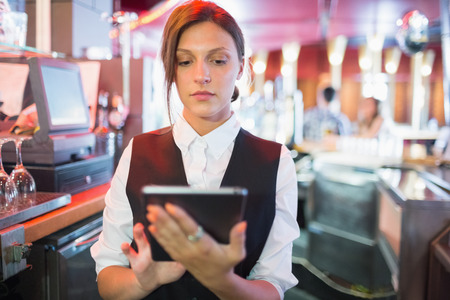 to till: Focused barmaid using touchscreen till in a bar