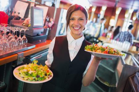 barra: Bastante camarera sosteniendo platos de ensaladas en un bar