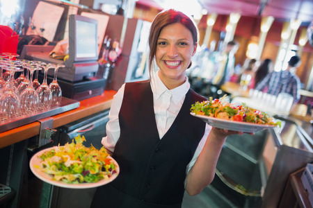 Pretty barmaid holding plates of salads in a bar Archivio Fotografico