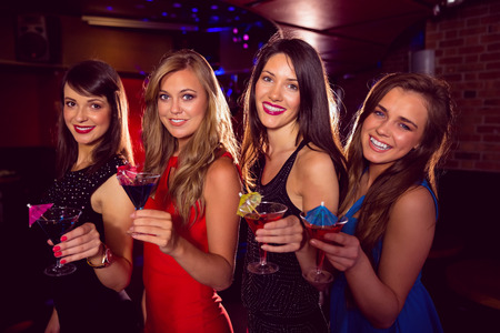 nightclub: Pretty friends drinking cocktails together at the nightclub Stock Photo