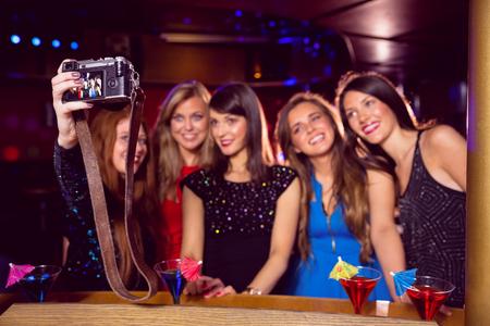 tomando refresco: Amigos bonita que toma un Autofoto en el club nocturno Foto de archivo