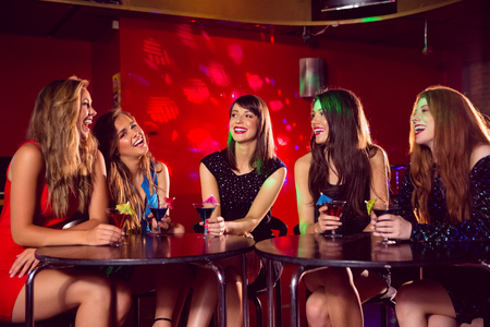 pretty dress: Pretty friends drinking cocktails together at the nightclub Stock Photo