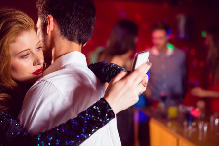 Cute couple slow dancing together at the nightclub photo
