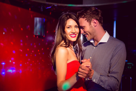 happy young couple: Cute couple slow dancing together at the nightclub Stock Photo