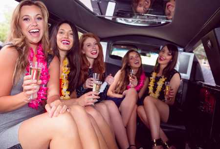 limo: Happy friends drinking champagne in limousine on a night out