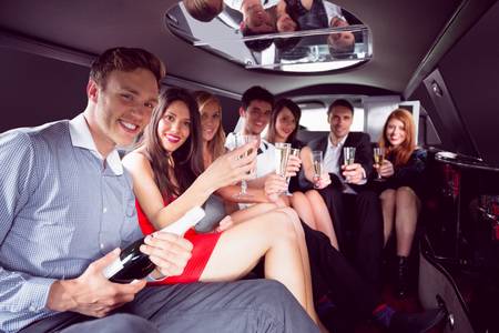 limousine: Happy friends drinking champagne in limousine on a night out