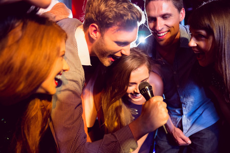 celebration event: Happy friends singing karaoke together at the nightclub