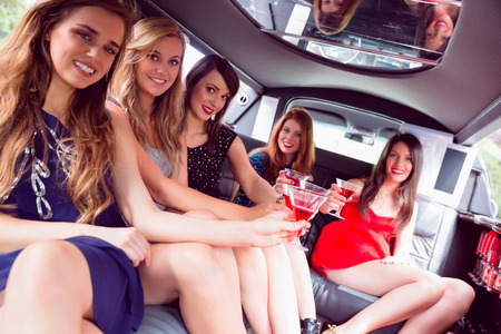 night out: Happy friends drinking cocktails in limousine on a night out