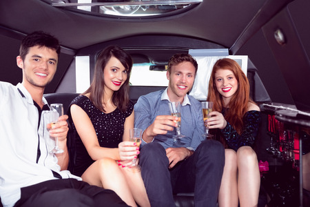 well dressed  holding: Happy friends drinking champagne in limousine on a night out