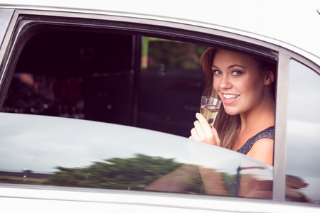 limo: Beautiful blonde drinking champagne limousine on a sunny day