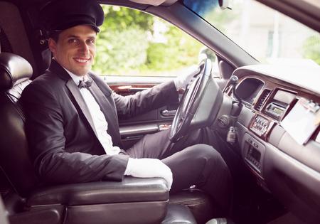chofer: Conductor de limusina sonriendo a la cámara en su limusina Foto de archivo