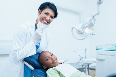 dentist drill: Portrait of smiling female dentist examining boys teeth in the dentists chair