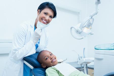 dentista: Retrato de la sonrisa mujer dentista examinando los dientes de los muchachos en la silla de los dentistas