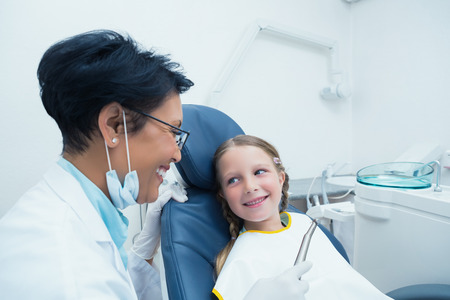 dentist mask: Female dentist examining girls teeth in the dentists chair Stock Photo