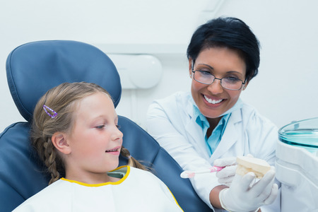 Female dentist teaching girl how to brush teeth in the dentists chair Stock Photo