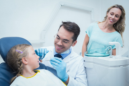 Dentist examining girls teeth in the dentists chair with assistant photo