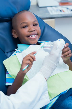 Dentist teaching happy boy how to brush teeth in the dentists chair photo