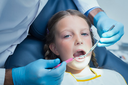 examined: Close up of girl having her teeth examined by a dentist