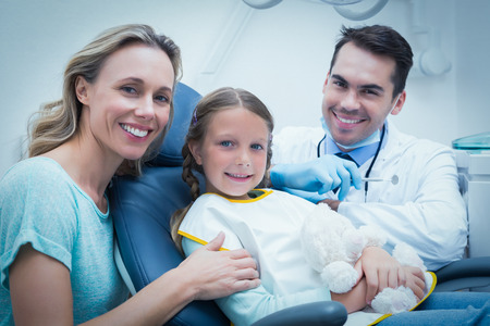 Dentist examining girls teeth in the dentists chair with assistant Stock Photo