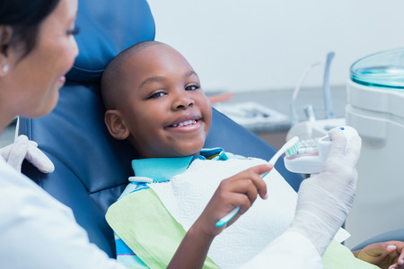 Dentist teaching happy boy how to brush teeth in the dentists chair