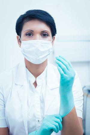 short gloves: Portrait of female dentist wearing surgical mask and gloves
